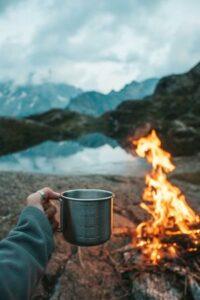 Camper mit Tasse an Lagerfeuer